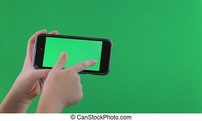 Child hands using a smart phone. chroma key, green screen -...