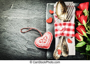 St Valentine's table setting with red roses and decorative...