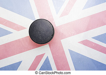 old hockey puck is on the ice with great britain flag