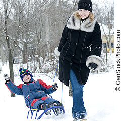 Mother pulling son on sledge, bright and white winter scene