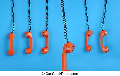 Orange telephones over blue background - Close-up large...