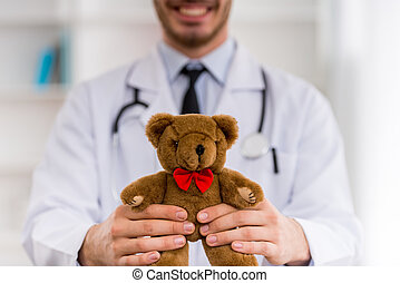Young happy pediatrician - Smiling doctor with a teddy bear...