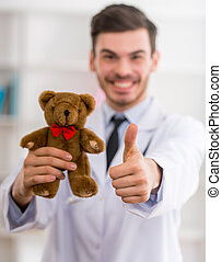 Young happy pediatrician - Smiling doctor with teddy bear in...