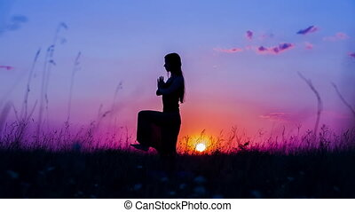 Young Woman Doing Yoga At Sunset - Shot of a silhouette of a...