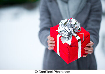 Close up red christmas box gift in winter day outdoors