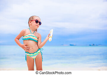 Little adorable girl applying sun cream during beach...