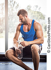 Man sitting on bench and drinking water - Young adult...