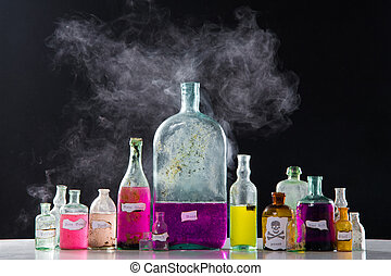 Magic spells in antique bottles over black background and...