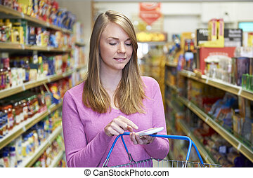 Woman Reading Shopping List From Smartphone In Supermarket