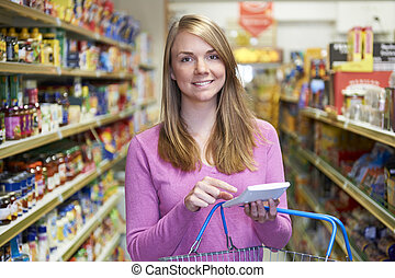 Woman Using Calculator Whilst Shopping In Supermarket