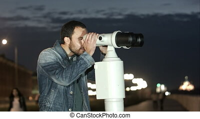Man using a coin operated telescope enjoying a great view of the city