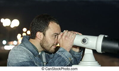 Young man looking through coin operated binoculars....