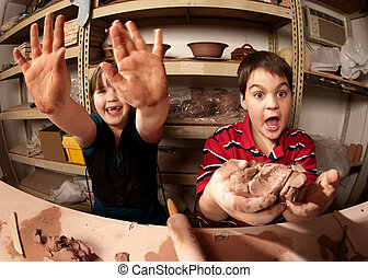 Children in a clay studio - Two cute kids working with clay...