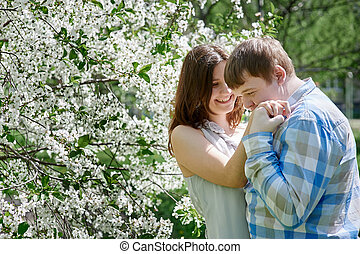 young man kissing a woman and 39;s hand in the blossoming...