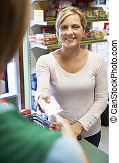 Customer Paying For Shopping With Voucher