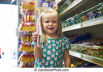 Happy Child At Candy Counter Of Supermarket