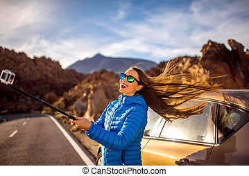 Woman making selfie portrait near the car - Young woman in...