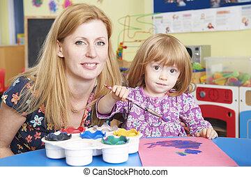 Teacher Helping Pre School Pupil In Art Class