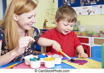 Teacher Helping Preschool Child In Art Class
