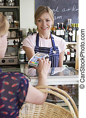 Customer Paying For Shopping In Delicatessen Using Credit...