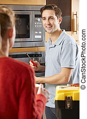 Engineer Giving Advice To Woman On Cooker Repair