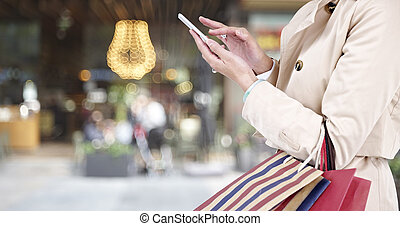 woman using cellphone while shopping - hands of a young...