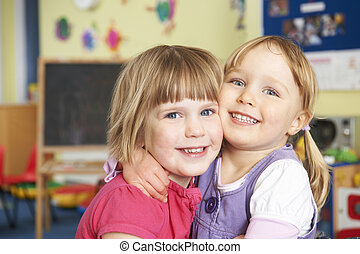 Two Female Pre School Pupils Hugging One Another