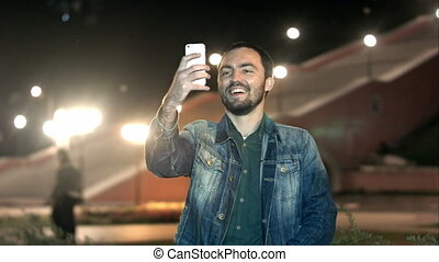Young handsome man looking at smartphone and taking selfie...