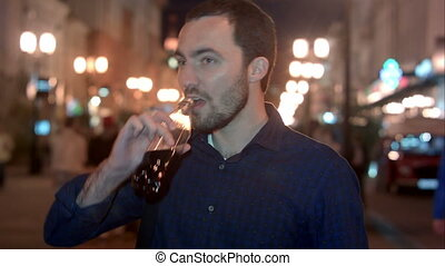 Young man drinking coke at night city. Professional shot on...