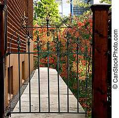 forged iron gate leading to a beautiful backyard - forged...