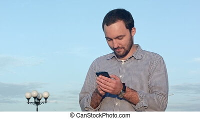 Man holding mobile smartphone using app texting sms message...