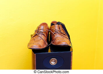 groom brown wedding shoes on speaker Yellow background -...