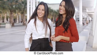 Two chic young women standing chatting together on an urban...