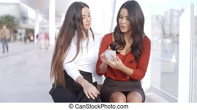 Young woman sharing a text message with a friend - Smiling...