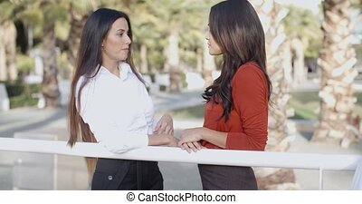 Two young ladies standing talking outdoors alongside a rail...