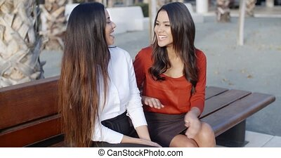 Two young women sharing a good joke - Two stylish young...