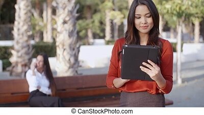 Young businesswoman using a tablet outdoors - Stylish...