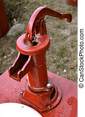 Old hand pump - A red painted old hand pump is used to bring...