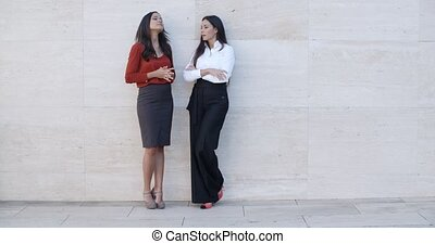 Two young women leaning on a wall chatting