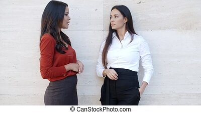 Two relaxed confident ladies standing chatting - Two relaxed...