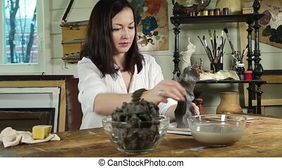 Artist woman sculpts from a clay in - Dolly video shot of an...