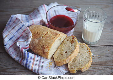 Freshly baked bread served with jam and glass of milk -...