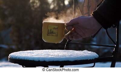 a cup with hot tea on a snow-covered chair - the person puts...