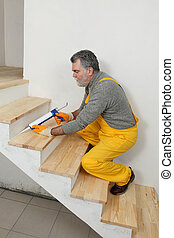 Home renovation, caulking wooden stairs with silicone