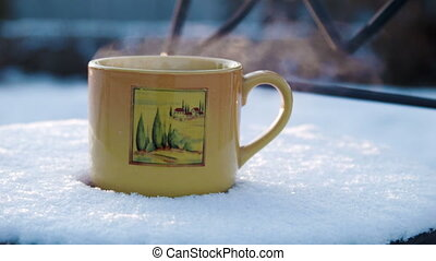 a cup with hot tea on a snow-covered chair - Cup with hot...