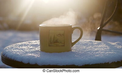 Cup with hot tea against the sun in the winter - Cup with...