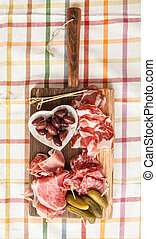 Selection of hams and salami on vintage wooden cutting board