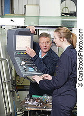 Apprentice And Engineer Using Computer Controlled Cutting...