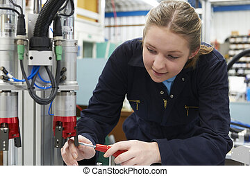 Female Apprentice Engineer Working On Machine In Factory