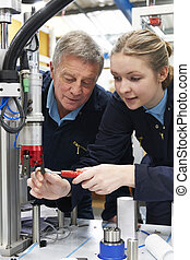 Engineer And Female Apprentice Working On Machinery In Factory